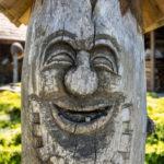 Ul wyrzeźbiony z drewnianego pnia w kształcie uśmiechniętej twarzy.