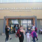 Kilkoro dzieci stoi przed wejściem do zbytkowej kopalni srebra w Tarnowskich Górach.