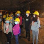 Dzieci zwiedzają szyb kopalni, słuchają przewodnika.