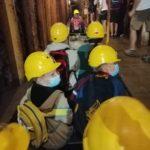 Wychowankowie w żółtych kaskach płyną łodziami przy szybie kopalni.
