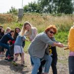 Wychowawcy i wychowankowie w trakcie zabawy w przeciąganie liny.