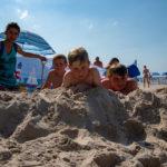 Dzieci leżące na plaży pomiędzy dwoma wychowawczyniami zakopanymi w piasku.