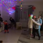 Wychowankowie podczas zabawy. Na pierwszym planie troje dziewcząt tańczy w kółeczku wewnątrz którego w którym w środku jest wychowanek. Po ich prawej stronie tańczy kobieta z małym chłopcem przebranym za Spidermena.