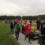 Wychowankowie na cmentarzu idą chodnikiem obok grobów.