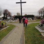 Dwie dziewczynki w masczkach stoją przed drewnianym krzyżem na cmentarzu.