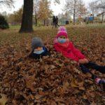 Dwoje dzieci siedzi na ziemi w jesiennych liściach.
