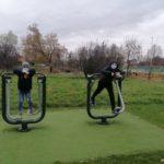 Dwóch wychowanków ćwiczy na siłowni na świeżym powietrzu. Korzystają z urządzenia a nazwie biegacz.